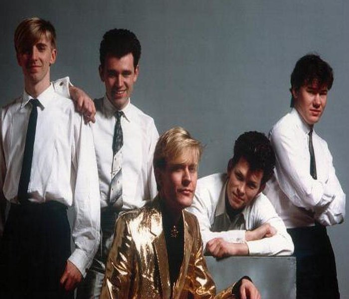 "Martin Fry the lead singer of the Uk band that is - ""ABC"" - He is the one with the ""Gold"" suite in the middle of the picture"